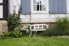 Gartenbank Holz weiß an Hauswand hinterm Haus