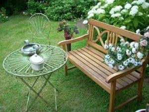 Gartenbank Holz braun mit Rückenlehne dekoriert mit Margaritten freistehend